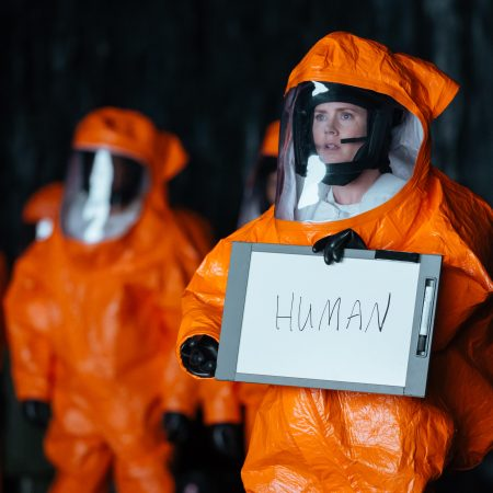 "A scientist in orange protective suit holds a sign saying ""human"""