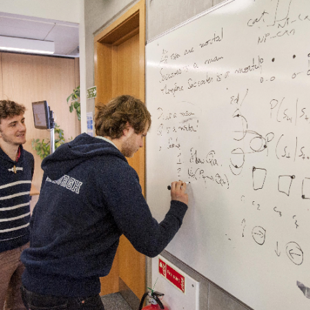 Two students writing equations on whiteboard
