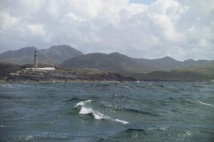 Waves surrounded by Scottish hills and a lighthouse