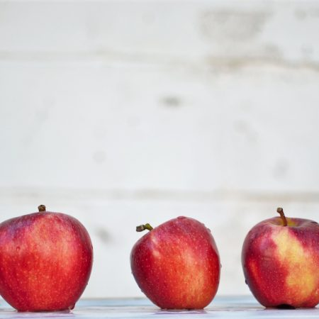 a row of red apples of different sizes in front of grey background